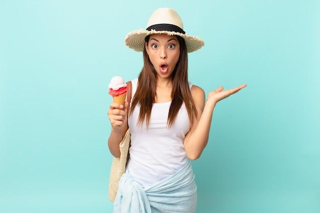Młoda latynoska kobieta wyglądająca na zaskoczoną i zszokowaną, z opuszczoną szczęką, trzymająca przedmiot i trzymającego lody. koncepcja suma