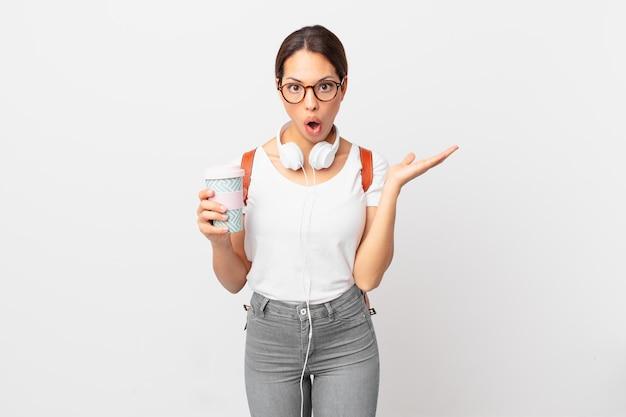 Młoda latynoska kobieta wyglądająca na zaskoczoną i zszokowaną, z opuszczoną szczęką trzymająca przedmiot. koncepcja studenta