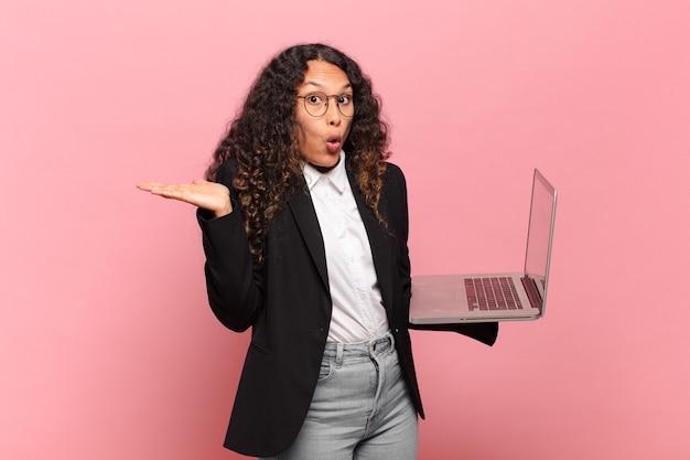 Młoda latynoska kobieta wyglądająca na zaskoczoną i zszokowaną, z opuszczoną szczęką, trzymająca przedmiot z otwartą dłonią z boku. laptop