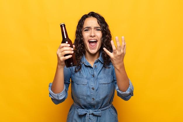 Młoda latynoska kobieta wyglądająca na zdesperowaną i sfrustrowaną, zestresowaną, nieszczęśliwą i zirytowaną, krzyczącą i wrzeszczącą