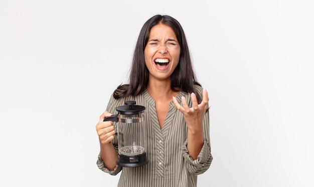 Młoda latynoska kobieta wyglądająca na zdesperowaną, sfrustrowaną i zestresowaną, trzymającą ręczny ekspres do kawy