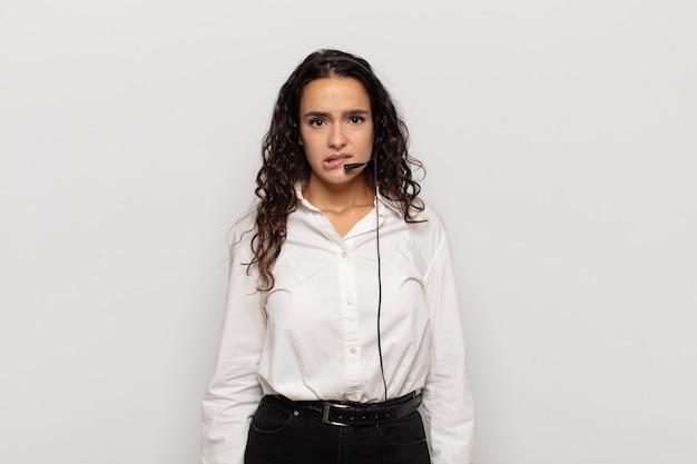 Młoda latynoska kobieta wyglądająca na zdziwioną i zdezorientowaną, przygryza wargę nerwowym gestem, nie znając odpowiedzi na problem