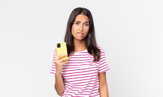 Młoda latynoska kobieta wyglądająca na zdziwioną i zdezorientowaną, trzymająca smartfona