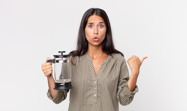 Młoda latynoska kobieta wyglądająca na zdziwioną z niedowierzaniem i trzymająca ręczny ekspres do kawy