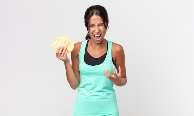 Młoda latynoska kobieta wyglądająca na złą, zirytowaną i sfrustrowaną. koncepcja diety fitness