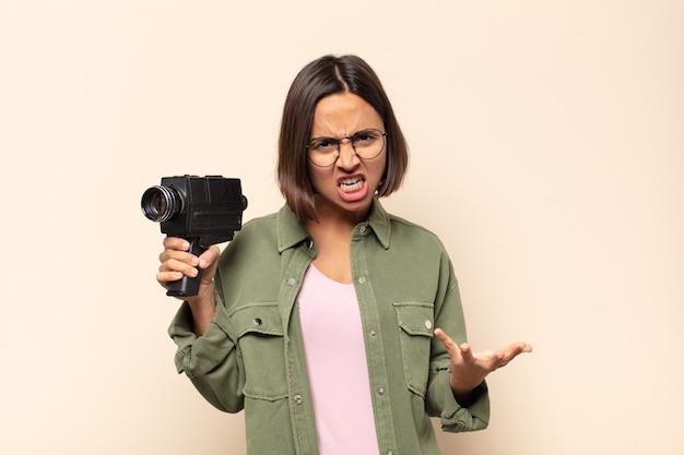 Młoda latynoska kobieta wyglądająca na złą, zirytowaną i sfrustrowaną, krzycząc wtf lub co jest z tobą nie tak