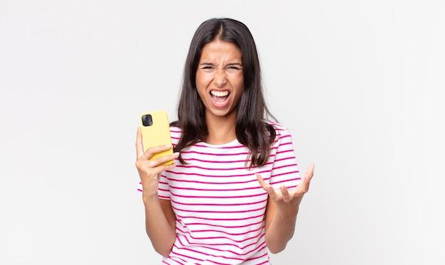 Młoda latynoska kobieta wyglądająca na złą, zirytowaną i sfrustrowaną, trzymająca smartfona