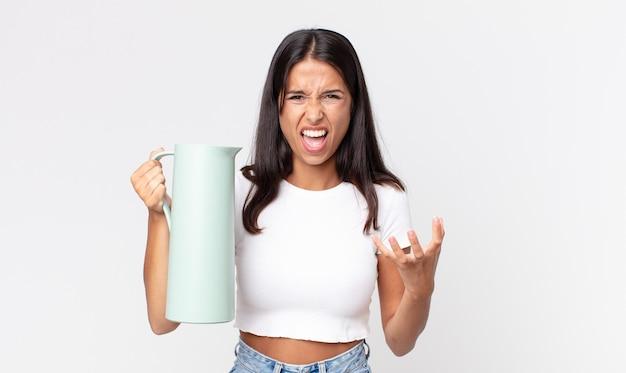 Młoda latynoska kobieta wyglądająca na złą, zirytowaną i sfrustrowaną, trzymająca termos z kawą