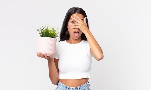 Młoda latynoska kobieta wyglądająca na zszokowaną, przestraszoną lub przerażoną, zakrywa twarz dłonią i trzyma ozdobną roślinę domową