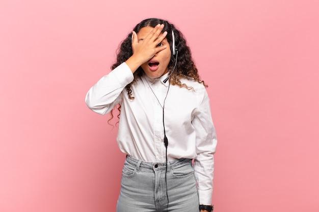 Młoda latynoska kobieta wyglądająca na zszokowaną, przestraszoną lub przerażoną, zakrywa twarz dłonią i zerka między palcami. koncepcja telemarketera