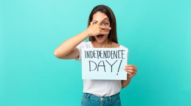 Młoda latynoska kobieta wyglądająca na zszokowaną, przestraszoną lub przerażoną, zakrywając twarz dłonią. koncepcja dnia niepodległości