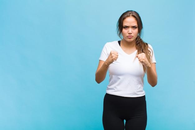 Młoda latynoska kobieta wyglądająca pewnie, wściekle, silna i agresywna, z pięściami gotowymi do walki w pozycji bokserskiej