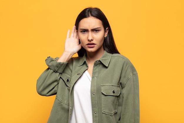 Młoda latynoska kobieta wyglądająca poważnie i zaciekawiona, słuchająca, próbująca usłyszeć tajną rozmowę lub plotkę, podsłuchująca