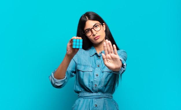 Młoda latynoska kobieta wyglądająca poważnie, surowo, niezadowolona i wściekła pokazuje otwartą dłoń wykonującą gest stopu. koncepcja problemu inteligencji