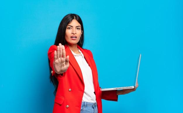Młoda latynoska kobieta wyglądająca poważnie, surowo, niezadowolona i wściekła pokazuje otwartą dłoń wykonującą gest stopu