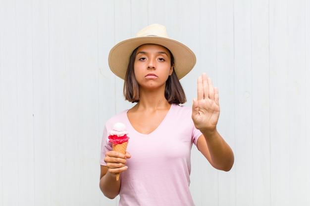 Młoda latynoska kobieta wyglądająca poważnie, surowo, niezadowolona i zła, pokazując otwartą dłoń wykonującą gest stop