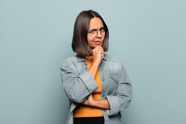 Młoda latynoska kobieta wyglądająca poważnie, zdezorientowana, niepewna i zamyślona, wątpiąca w opcje lub wybory