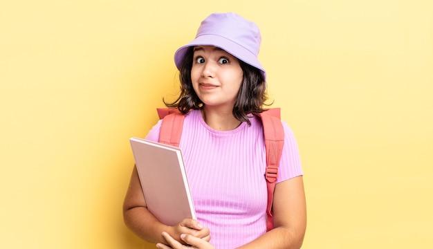 Młoda latynoska kobieta wzrusza ramionami, czując się zdezorientowana i niepewna. powrót do koncepcji szkoły