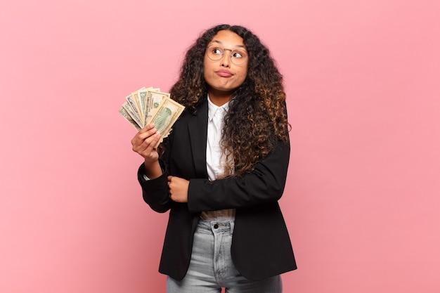 Młoda latynoska kobieta wzrusza ramionami, czując się zdezorientowana i niepewna, wątpiąca ze skrzyżowanymi rękami i zdziwionym spojrzeniem. koncepcja banknotów dolarowych