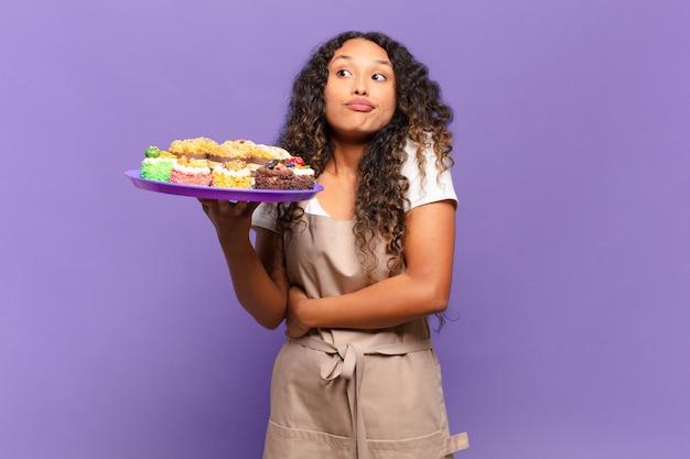 Młoda latynoska kobieta wzrusza ramionami, czując się zdezorientowana i niepewna, wątpiąca ze skrzyżowanymi rękami i zdziwionym spojrzeniem. koncepcja gotowania ciast