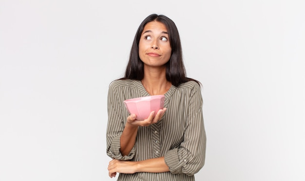 Młoda latynoska kobieta wzrusza ramionami, czuje się zdezorientowana i niepewna, trzymając pustą miskę lub garnek