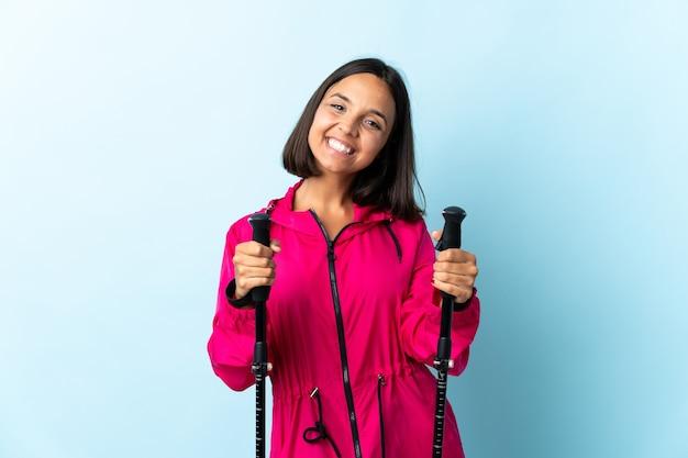 Młoda latynoska kobieta z plecakiem i kijkami trekkingowymi
