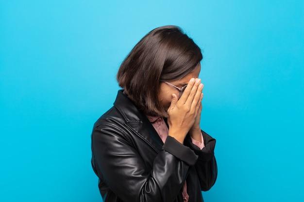 Młoda latynoska kobieta zakrywająca oczy dłońmi smutnym, sfrustrowanym wyrazem rozpaczy, płaczu, widoku z boku