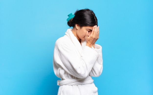 Młoda latynoska kobieta zakrywająca oczy rękami ze smutnym, sfrustrowanym spojrzeniem rozpaczy, płacz, widok z boku