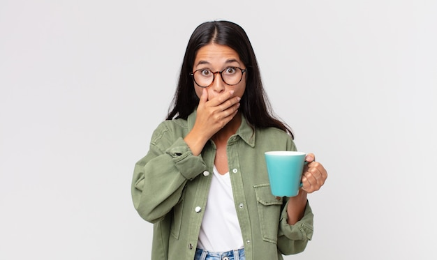 Młoda latynoska kobieta zakrywająca usta dłońmi zszokowana i trzymająca kubek z kawą