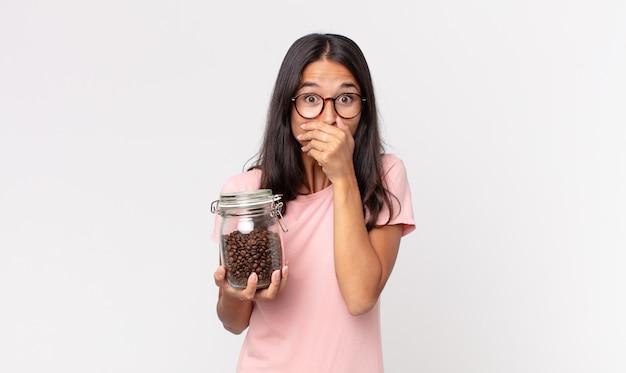 Młoda latynoska kobieta zakrywająca usta rękami zszokowana i trzymająca butelkę ziaren kawy