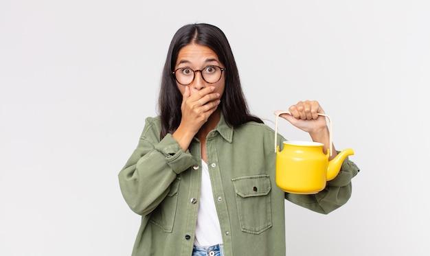 Młoda latynoska kobieta zakrywająca usta rękami zszokowana i trzymająca dzbanek do herbaty