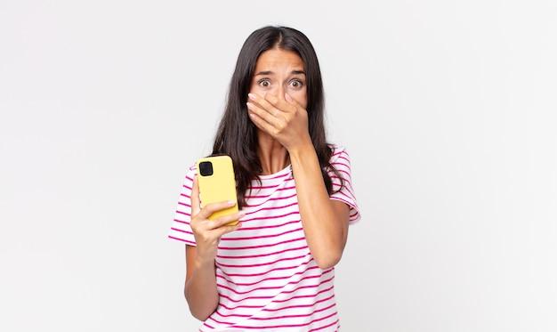 Młoda latynoska kobieta zakrywająca usta rękami zszokowana i trzymająca smartfon