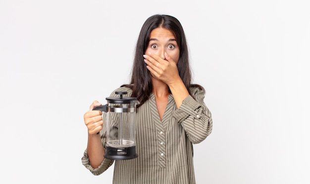 Młoda latynoska kobieta zakrywająca usta rękami zszokowanym i trzymająca ręczny ekspres do kawy