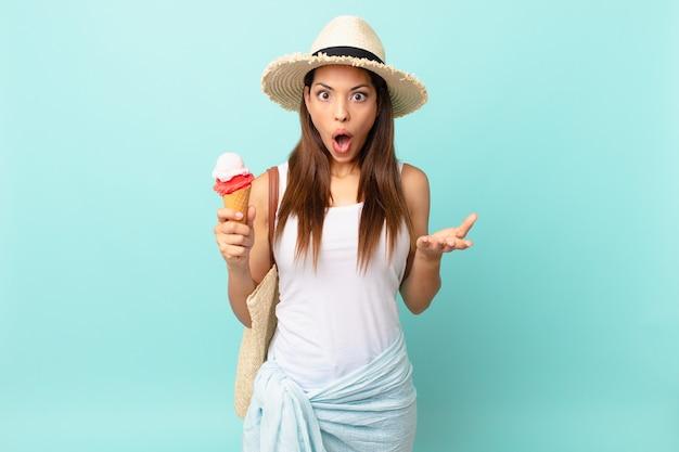 Młoda latynoska kobieta zdumiona, zszokowana i zdumiona niewiarygodnym zaskoczeniem i trzymająca lody. koncepcja suma