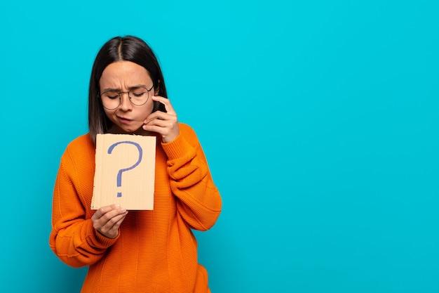 Młoda latynoska kobieta ze znakiem zapytania