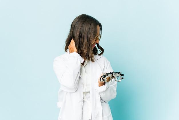 Młoda latynoska okulistka nad odizolowaną ścianą odczuwa ból szyi spowodowany stresem, masuje ją i dotyka ręką.