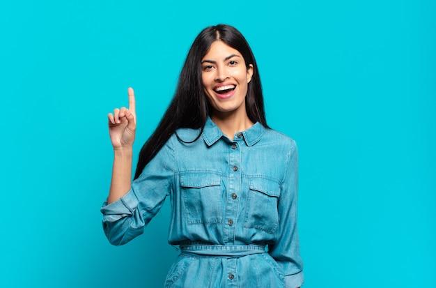 Młoda latynoska przypadkowa kobieta czująca się jak szczęśliwa i podekscytowana geniusz po zrealizowaniu pomysłu, radośnie podnosząca palec, eureka!