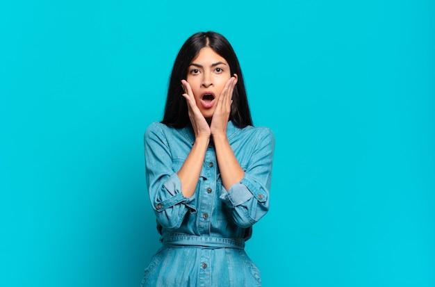 Młoda latynoska przypadkowa kobieta czuje się zszokowana i przestraszona, wygląda na przerażoną z otwartymi ustami i rękami na policzkach