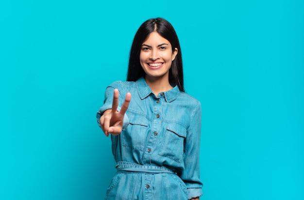 Młoda latynoska przypadkowa kobieta uśmiechająca się i wyglądająca przyjaźnie, pokazująca numer dwa lub drugi z ręką do przodu, odliczając w dół