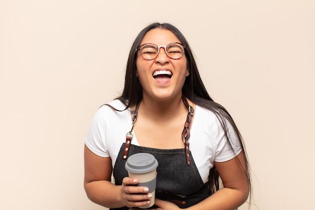 Młoda latynoska śmiejąca się głośno z jakiegoś przezabawnego żartu, szczęśliwa i wesoła, dobrze się bawi