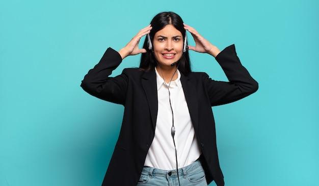 Młoda latynoska telemarketerka czuje się zestresowana, zmartwiona, niespokojna lub przestraszona, z rękami na głowie, panikując z powodu błędu