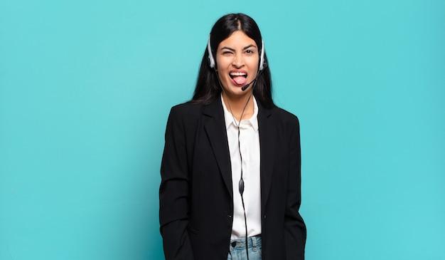 Młoda latynoska telemarketerka o wesołym, beztroskim, buntowniczym nastawieniu, żartuje i wystawia język, dobrze się bawi