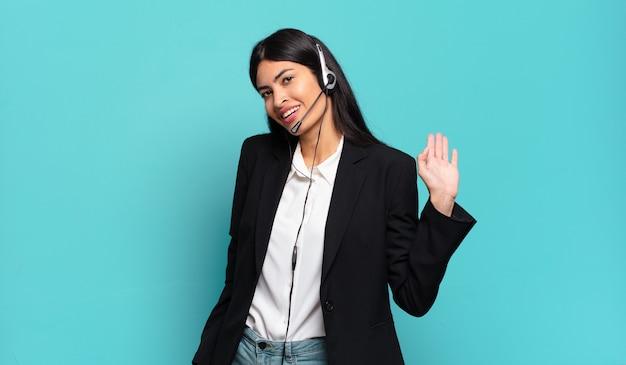 Młoda latynoska telemarketerka uśmiecha się radośnie i wesoło, macha ręką, wita i wita lub żegna się