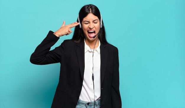 Młoda latynoska telemarketerka wygląda na niezadowoloną i zestresowaną, samobójczy gest robiący znak pistoletu ręką, wskazujący na głowę