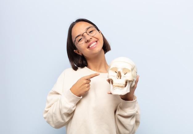 Młoda latynoska uśmiecha się radośnie, czuje się szczęśliwa i wskazuje na bok i do góry, pokazując obiekt w przestrzeni kopii