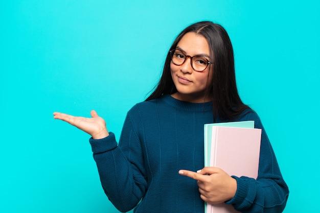 Młoda latynoska uśmiecha się radośnie i wskazuje, aby skopiować miejsce na dłoni z boku, pokazując lub reklamując przedmiot