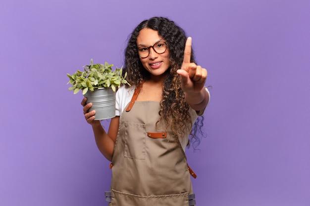 Młoda latynoska uśmiechnięta dumnie i pewnie w triumfującej pozie numer jeden, czując się jak przywódczyni. koncepcja ogrodnika