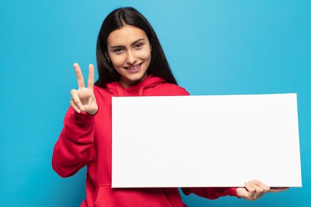 Młoda latynoska uśmiechnięta i wyglądająca na szczęśliwą, beztroską i pozytywną, gestykulującą jedną ręką zwycięstwo lub pokój