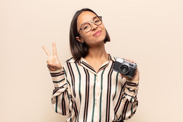 Młoda latynoska uśmiechnięta i wyglądająca na szczęśliwą, beztroską i pozytywną, gestykulującą zwycięstwo lub pokój jedną ręką