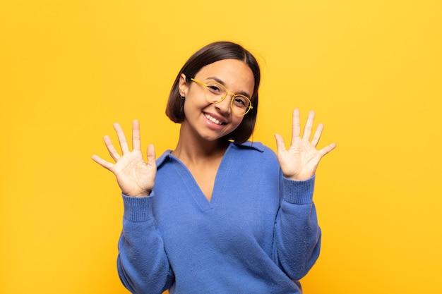 Młoda latynoska uśmiechnięta i wyglądająca przyjaźnie, pokazująca numer dziesięć lub dziesiątą z ręką do przodu, odliczająca w dół